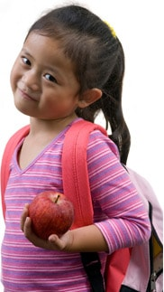 School girl with backpack holding apple